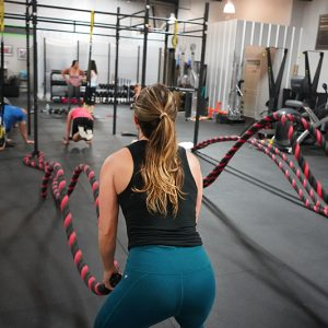Kvinne som trener Crossfit med rep