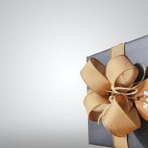 gave innpakket i grått papir og gull sløyfe